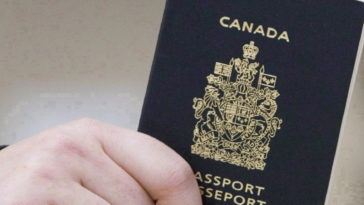 A passenger holds a Canadian passport before boarding a flight in Ottawa on Jan 23, 2007. Federal officials used photo-matching technology to identify 15 high-risk people - all wanted on immigration warrants - who used false identities to apply for travel documents. THE CANADIAN PRESS/Tom Hanson
